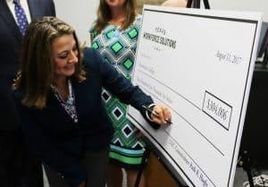TWC Commissioner Hughs signing JET grant check